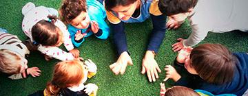 Niños jugando en el suelo con su profesora