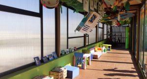 Mesas y sillas junto a los ventanales del colegio