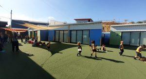 Alumnos jugando en el patio de césped