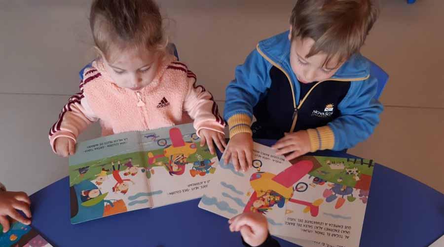 Alumna y alumno de 2 años leyendo un libro