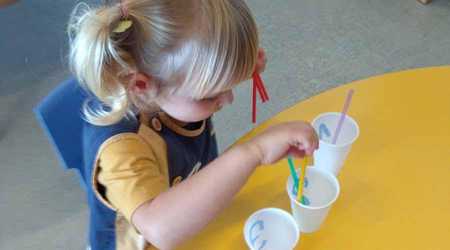 Niña de 2 años experimentando con vasos de plástico